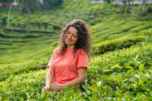 Schönes brünettes mädchen, das in der mitte des teetals zwischen grünen teebüschen aufwirft. Premium Fotos
