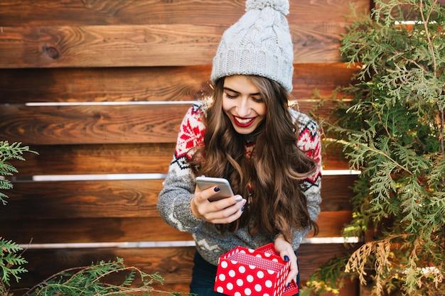 Schönes brünettes mädchen mit langen haaren und roten lippen auf hölzernem freien. sie trägt eine strickmütze, ein telefon und eine geschenkbox. sie sieht glücklich aus. Kostenlose Fotos