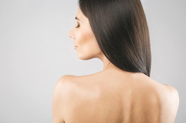 Schönes brünettes mädchen mit langen und glatten braunen haaren. glänzendes glattes und gesundes gepflegtes haar. isoliert über weißem hintergrund. Premium Fotos