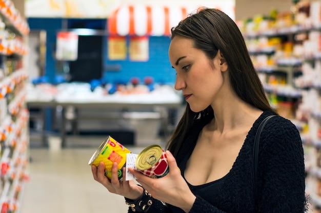 Schönes brunettefraueneinkaufen im supermarkt. auswahl von gentechnikfreien lebensmitteln. Premium Fotos