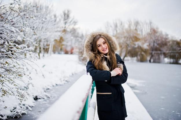 Schönes brunettemädchen in der warmen kleidung des winters. modell auf winterjacke gegen gefrorenen see am park. Premium Fotos