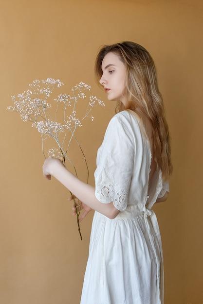 Schönes dünnes junges mädchen mit dem langen haar im weißen kleid mit der blanken rückseite, die auf beige hintergrund aufwirft und weiße blumen in ihren händen hält Premium Fotos