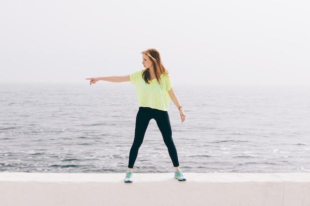 Schönes dünnes mädchen in der grünen sportkleidung zeigt die richtung der hand auf dem hintergrund des meeres Premium Fotos