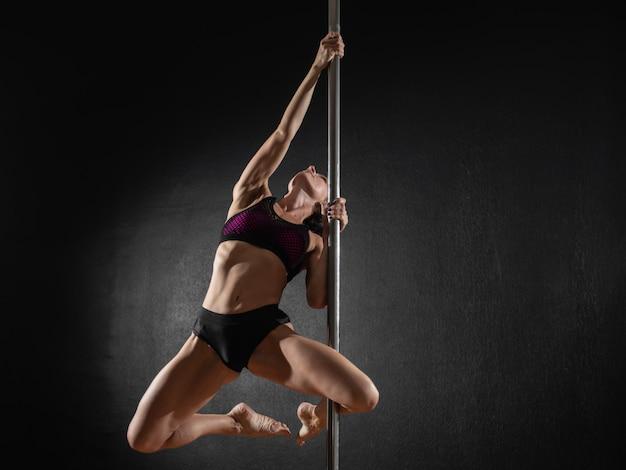 Schönes dünnes mädchen mit mast. weibliches stangentänzertanzen auf einem schwarzen hintergrund Premium Fotos