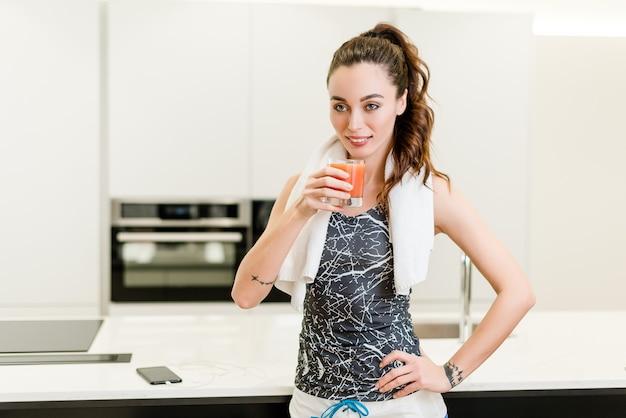 Schönes eignungsmädchen, das frischen saft an der küche trinkt Premium Fotos