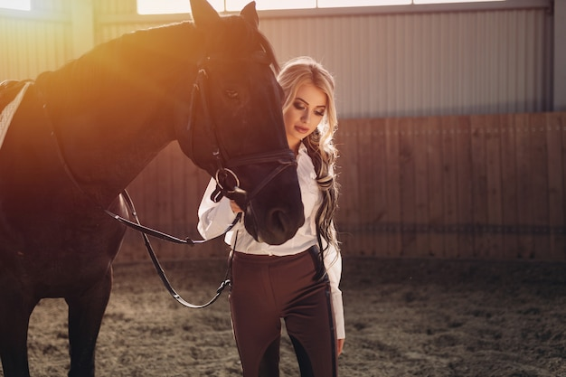 Schönes elegantes junges blondes mädchen, das nahe ihrem pferd kleidet uniformwettbewerb steht Premium Fotos