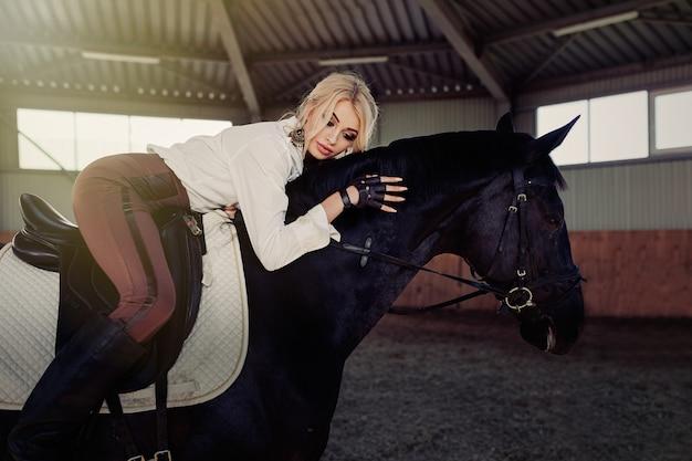 Schönes elegantes junges blondes mädchen liegt auf einer rappe, die weißes blusenhemd des einheitlichen wettbewerbs und braune hosen kleidet. Premium Fotos