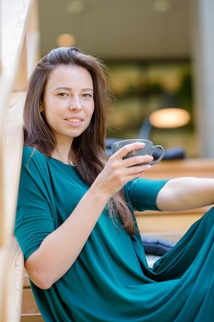 Schönes elegantes mädchen, das café am im freien frühstückt. trinkender kaffee der glücklichen jungen städtischen frau Premium Fotos