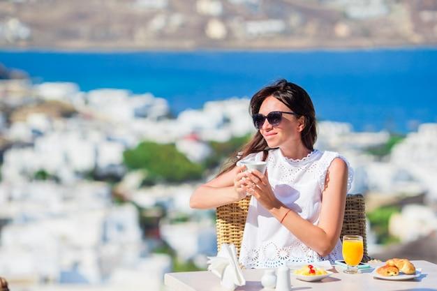 Schönes elegantes mädchen, das café am im freien mit erstaunlicher ansicht über mykonos-stadt frühstückt. frau, die heißen kaffee auf luxushotelterrasse mit seeansicht am erholungsortrestaurant trinkt. Premium Fotos