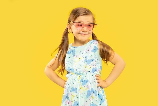 Schönes emotionales kleines mädchen isoliert. porträt des glücklichen kindes, das ein kleid und eine rote sonnenbrille steht und trägt. konzept des sommers, der menschlichen gefühle, der kindheit. Kostenlose Fotos