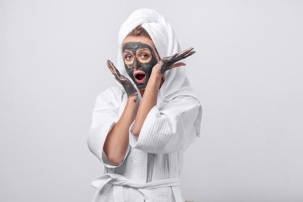 Schönes emotionales modell, das in einem weißen bademantel mit einem tuch auf ihrem kopf aufwirft Premium Fotos