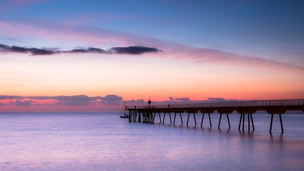 Schönes erwachen des himmels mit wenigen wolken und meer neben einem gehweg Premium Fotos