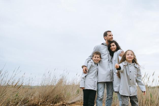 Schönes familienporträt gekleidet im regenmantel nahe dem see Premium Fotos