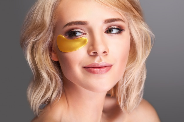 Schönes frauengesicht mit goldhydrogelflecken Premium Fotos