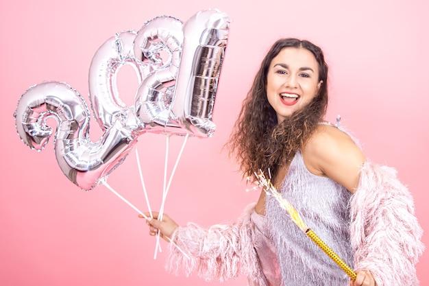 Schönes fröhliches festlich gekleidetes brünettes mädchen mit lockigem haar auf einem rosa studiohintergrund, der mit einer feuerwerkskerze in ihrer hand und silbernen luftballons für das neujahrskonzept aufwirft Kostenlose Fotos