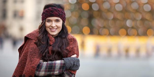 Schönes frohes frauenporträt in einer stadt. lächelndes mädchen, das warme kleidung und hut im winter oder im herbst trägt Premium Fotos