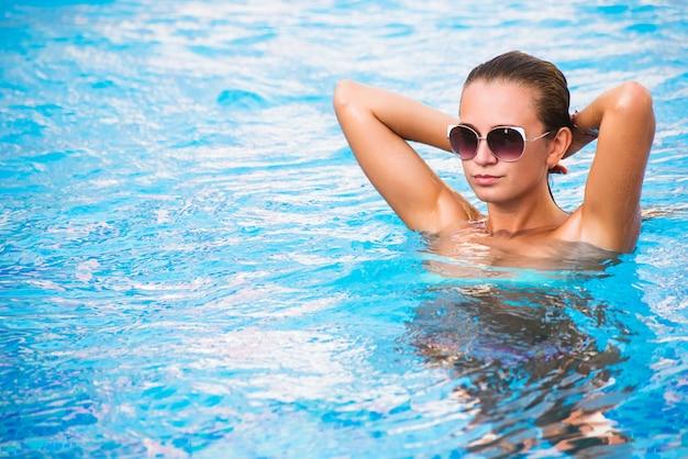 Schönes gebräuntes sexy mädchen im bikini, der im swimmingpool aufwirft Premium Fotos