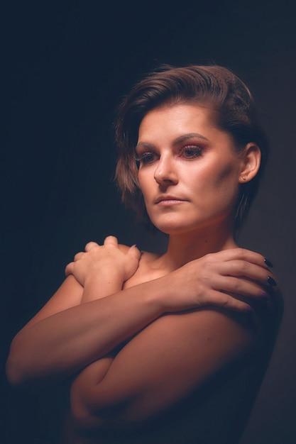 Schönes gesicht der jungen erwachsenen frau mit sauberer frischer haut. schwarzer hintergrund Premium Fotos