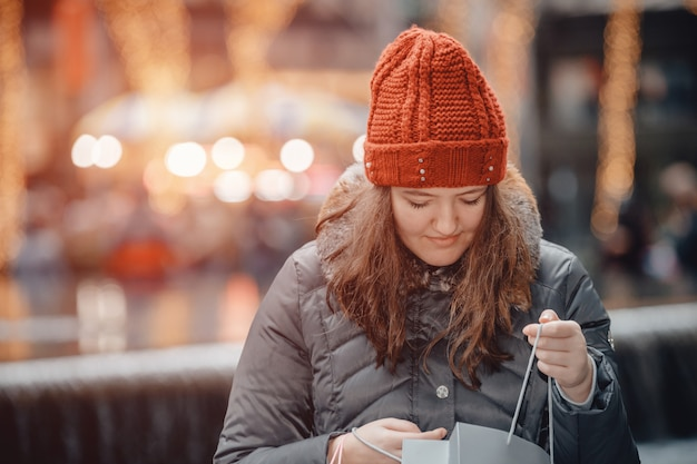Schönes glückliches mädchen geht nach dem einkauf in der stadt mit tüten einkaufen. Premium Fotos