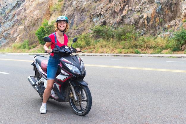 Schönes glückliches mädchen, junge frau, biker oder motorradfahrer reitet, fährt motorrad, moped oder fahrrad, lächelt. weiblicher reiter im helm auf der straße in den bergen an einem sommertag. Premium Fotos