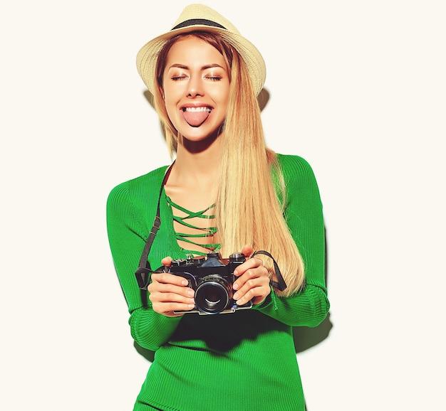 Schönes glückliches nettes blondes frauenmädchen in der zufälligen sommergrün-hippie-kleidung macht fotos, die retro- fotoapparat halten Kostenlose Fotos
