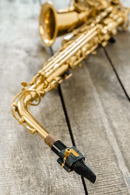 Schönes goldenes saxophon auf hölzernem hintergrund Premium Fotos