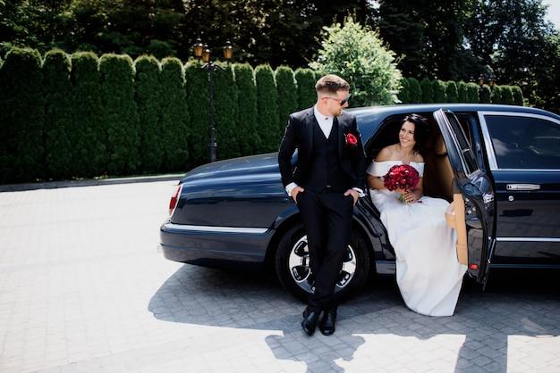 Schönes hochzeitspaar lächelt im schwarzen auto am sonnigen tag, gekleidet in eleganten hochzeitsoutfits mit rotem blumenstrauß Kostenlose Fotos
