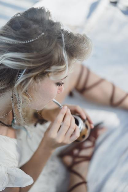 Schönes indisches hippiemädchen mit dem langen blonden haar auf trinkendem kameradentee des dachs. Kostenlose Fotos