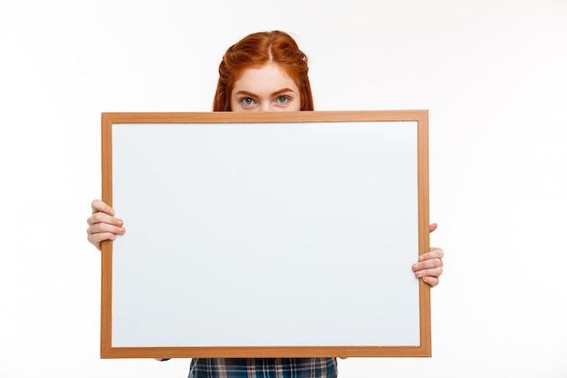Schönes ingwermädchen mit whiteboard über weißer wand. Kostenlose Fotos