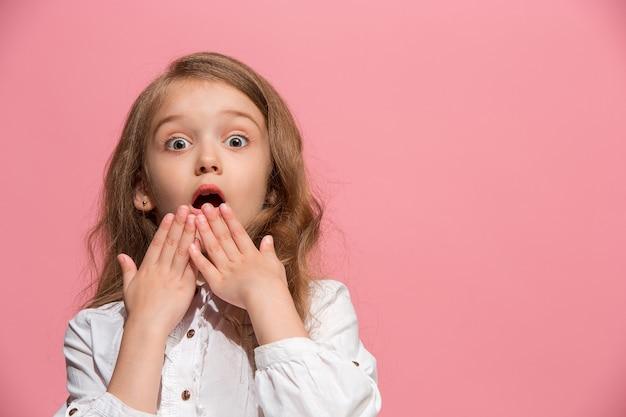 Schönes jugendlich mädchen, das auf rosa lokalisiert überrascht sieht Kostenlose Fotos