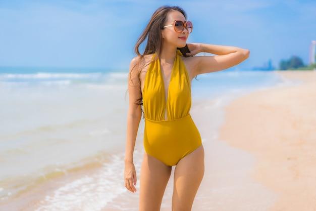 Schönes junges asiatisches frauenlächeln des porträts glücklich auf dem strand und dem meer Kostenlose Fotos
