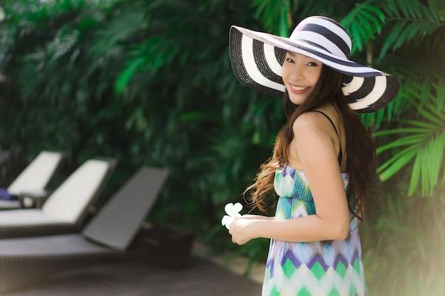 Schönes junges asiatisches frauenlächeln des porträts und glücklich um garten im freien Kostenlose Fotos