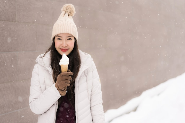 Schönes junges asiatisches frauenlächeln und glücklich mit eiscreme in der schneewintersaison Kostenlose Fotos