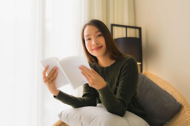 Schönes junges asiatisches frauenlesebuch des porträts und sitzen auf sofastuhl Kostenlose Fotos