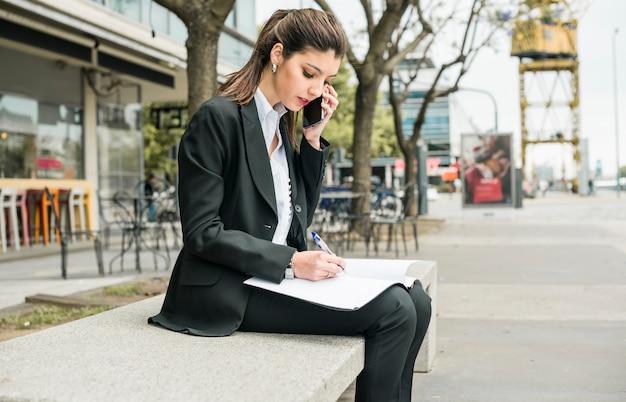 Schönes junges geschäftsfrauschreiben auf ordner mit stift bei der unterhaltung am handy Kostenlose Fotos