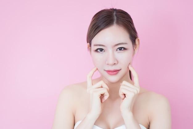 Schönes junges kaukasisches asiatisches frauenlächeln mit natürlichem make-up des sauberen frischen hautgesichtes. kosmetologie, hautpflege, gesichtsreinigung Premium Fotos