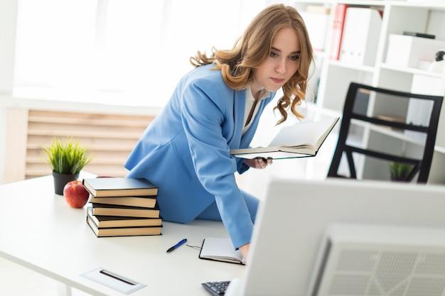 Schönes junges mädchen, das am schreibtisch im büro sitzt, ein buch in ihrer hand hält und den monitor betrachtet. Premium Fotos
