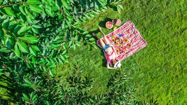 Schönes junges mädchen, das auf gras entspannt, sommerpicknick im park im freien habend Premium Fotos