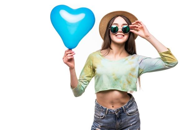 Schönes junges mädchen, das einen luftballon des blauen herzens hält. das konzept des valentinstags Kostenlose Fotos