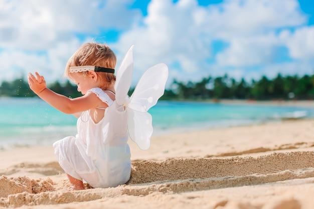 Schönes junges mädchen, das engelsflügel am strand trägt Premium Fotos