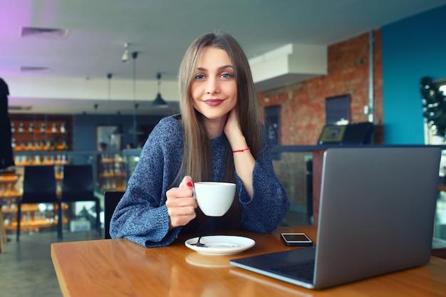 Schönes junges mädchen, das in einem café stillsteht Premium Fotos