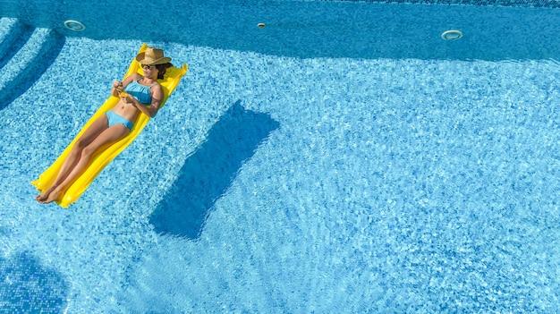 Schönes junges mädchen, das in schwimmbadfrau auf aufblasbarer matratze luftaufnahme entspannt Premium Fotos