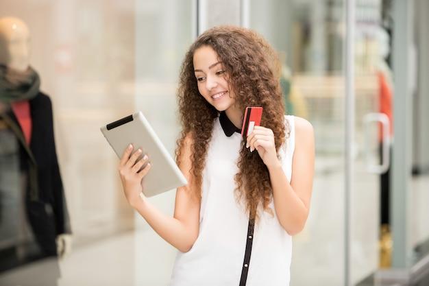 Schönes junges mädchen, das mit kreditkarte für das einkaufen zahlt Kostenlose Fotos