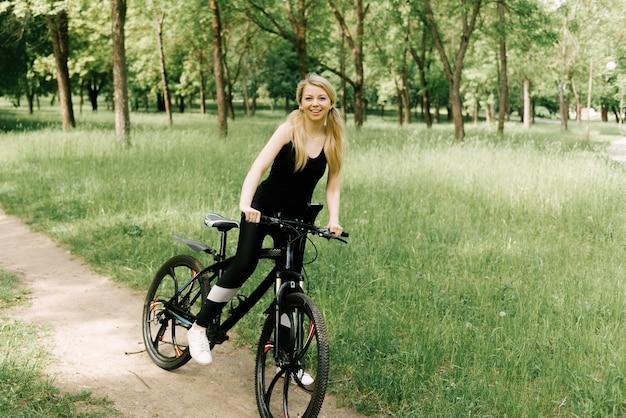 Schönes junges mädchen in der sportuniform, die ein fahrrad im park reitet Premium Fotos