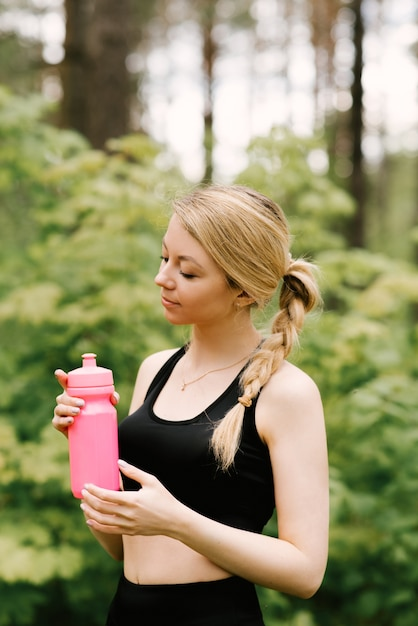 Schönes junges mädchen in der sportuniform mit einer flasche wasser, die yoga und sport im wald im freien tut Premium Fotos