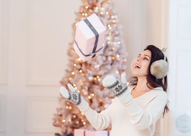 Schönes junges mädchen in einem weißen kleid wirft ein geschenk. Kostenlose Fotos