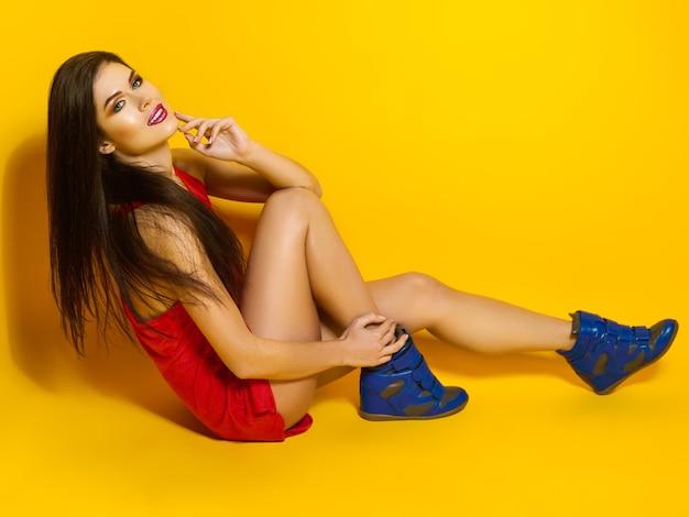 Schönes junges mädchen mit süßigkeiten in seinen händen lächelnd und posierend für ein foto, ein rotes t-shirt, schönes und gesundes haar, gelber hintergrund Premium Fotos