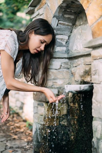 Schönes, junges mädchen trinkt das quellwasser, das im freien ist Kostenlose Fotos