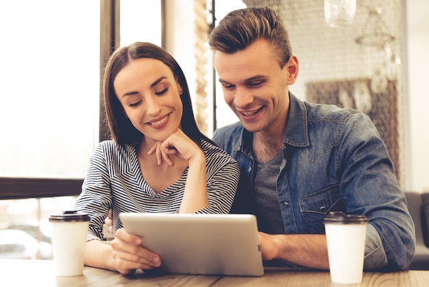 Schönes junges paar benutzt eine digitale tablette und ein lächeln Premium Fotos