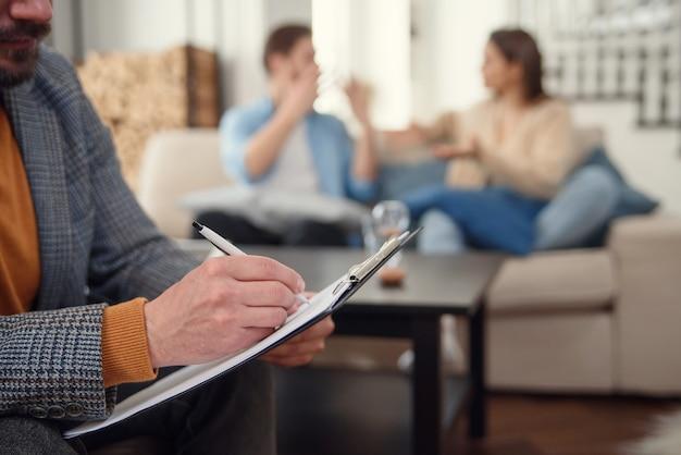 Schönes junges paar sitzt auf der couch und spricht mit dem psychologen, während arzt notizen macht Premium Fotos